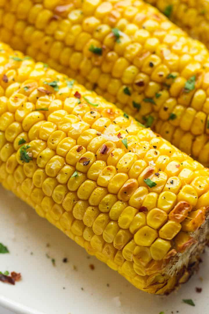 A close up shot of perfectly cooked and slightly charred corn on the cob that is seasoned with chopped parsley and sea salt flakes.