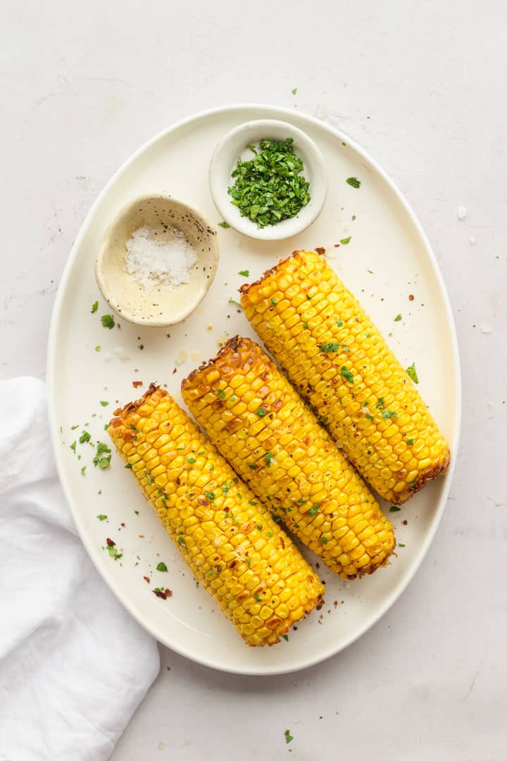 A white platter with three air fired  corn on the cob with sea salt flakes and chopped parsley in pinch bowls.