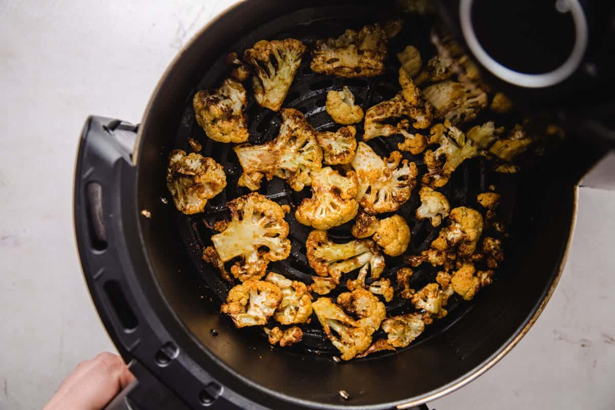 Roasted cauliflower florets in the air fryer basket after they were roasted.