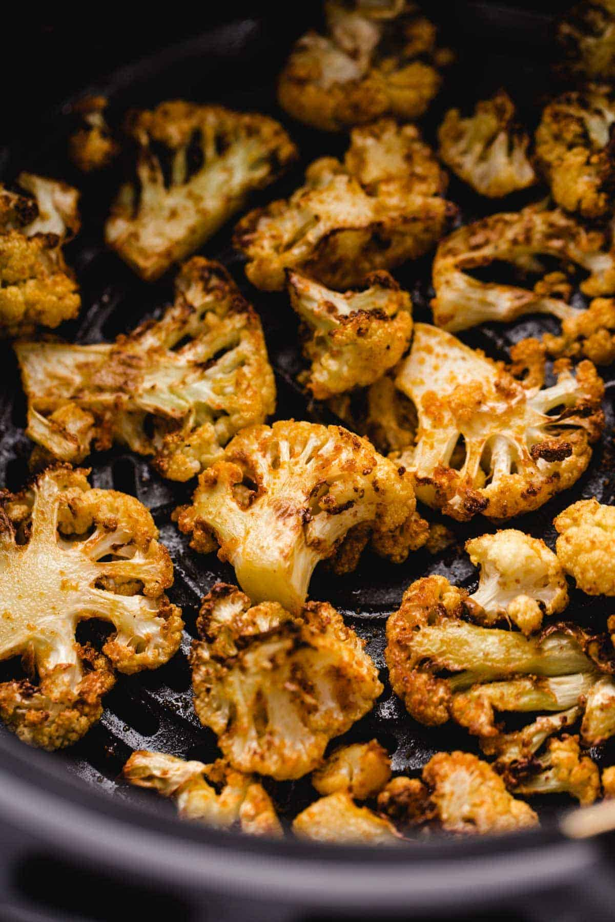 Roasted cauliflower florets in an air fryer basket.