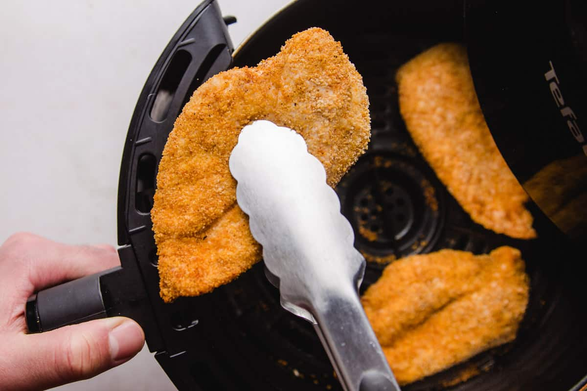 Taking out crispy chicken out of air fryer with kitchen tongs
