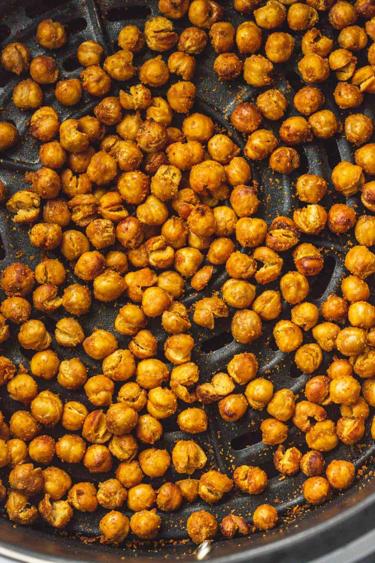 A close up image of air fryer chickpeas that are super crunchy in an air fryer basket.