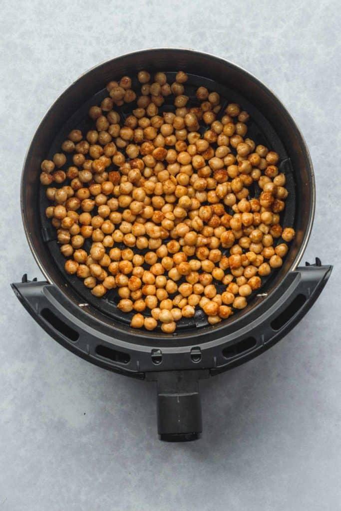 Seasoned chickpeas in an air fryer basket before roasting