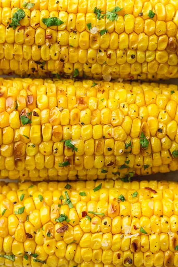 A close up shot of perfectly cooked and slightly charred corn on the cob 3 pieces