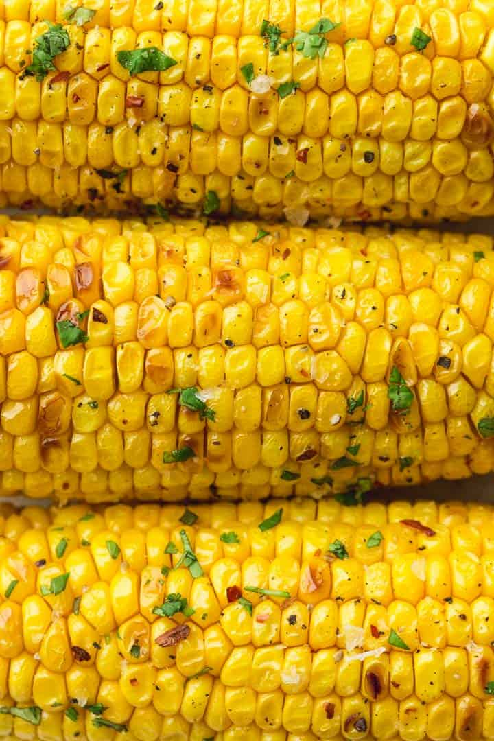 A close up shot of charred air fried three corn on the cob.