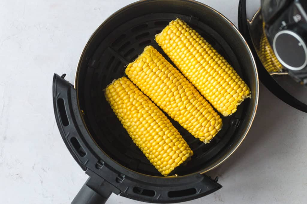 Placing corn on the cob in the air fryer basket