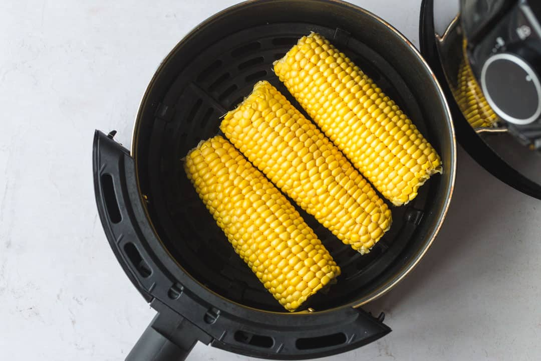 Placing three corn on the cob in the air fryer basket.
