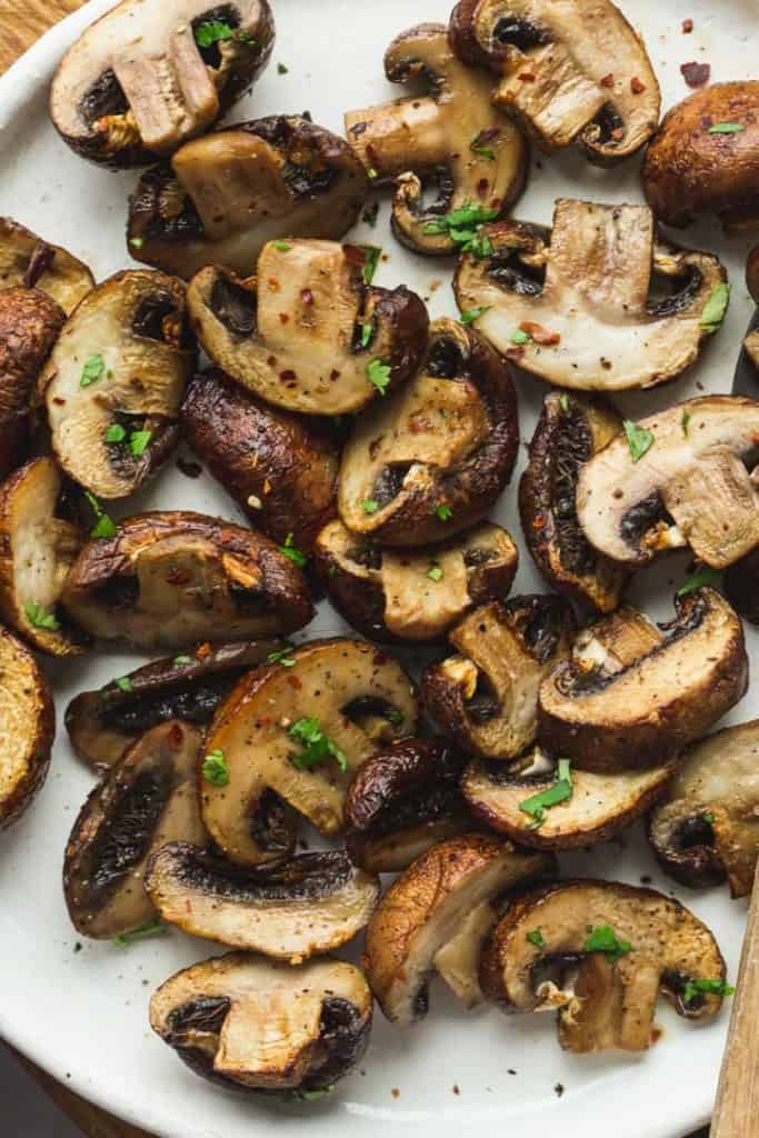 Air fried mushrooms with chopped parsley and chili flakes on a white plate