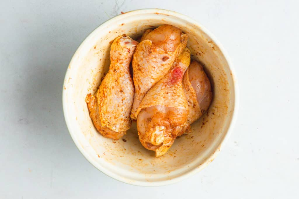 Raw and seasoned chicken legs in a bowl