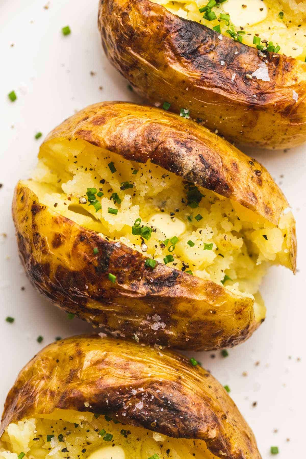 3 Baked Potatoes with butter, chopped chives, and sea salt flakes