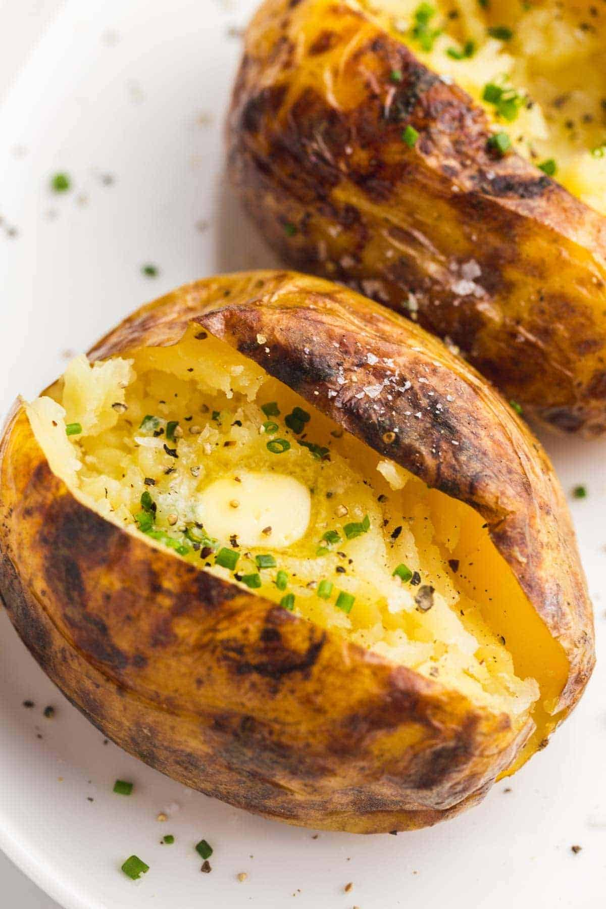 2 Baked Potatoes with butter, chopped chives, and sea salt flakes