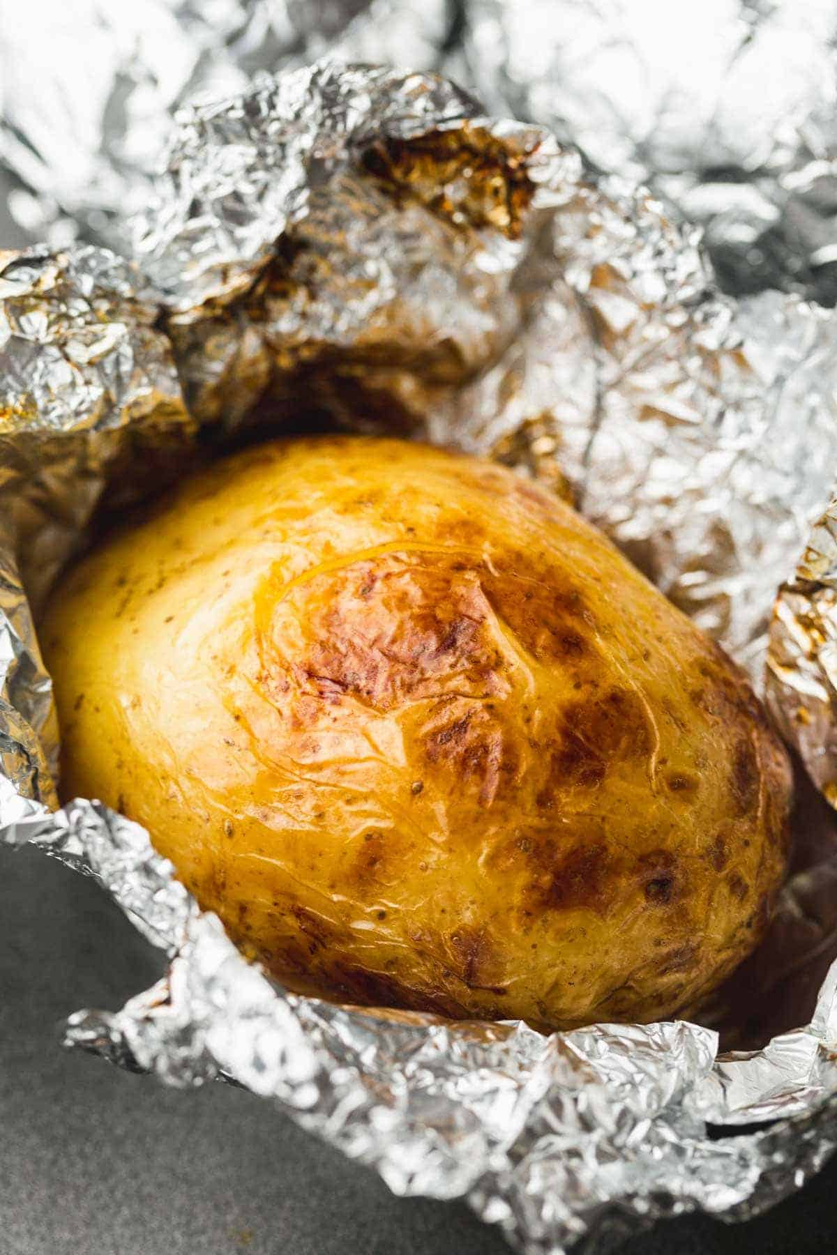 Baked potato on the grill is ready and unwrapped with crisp skin