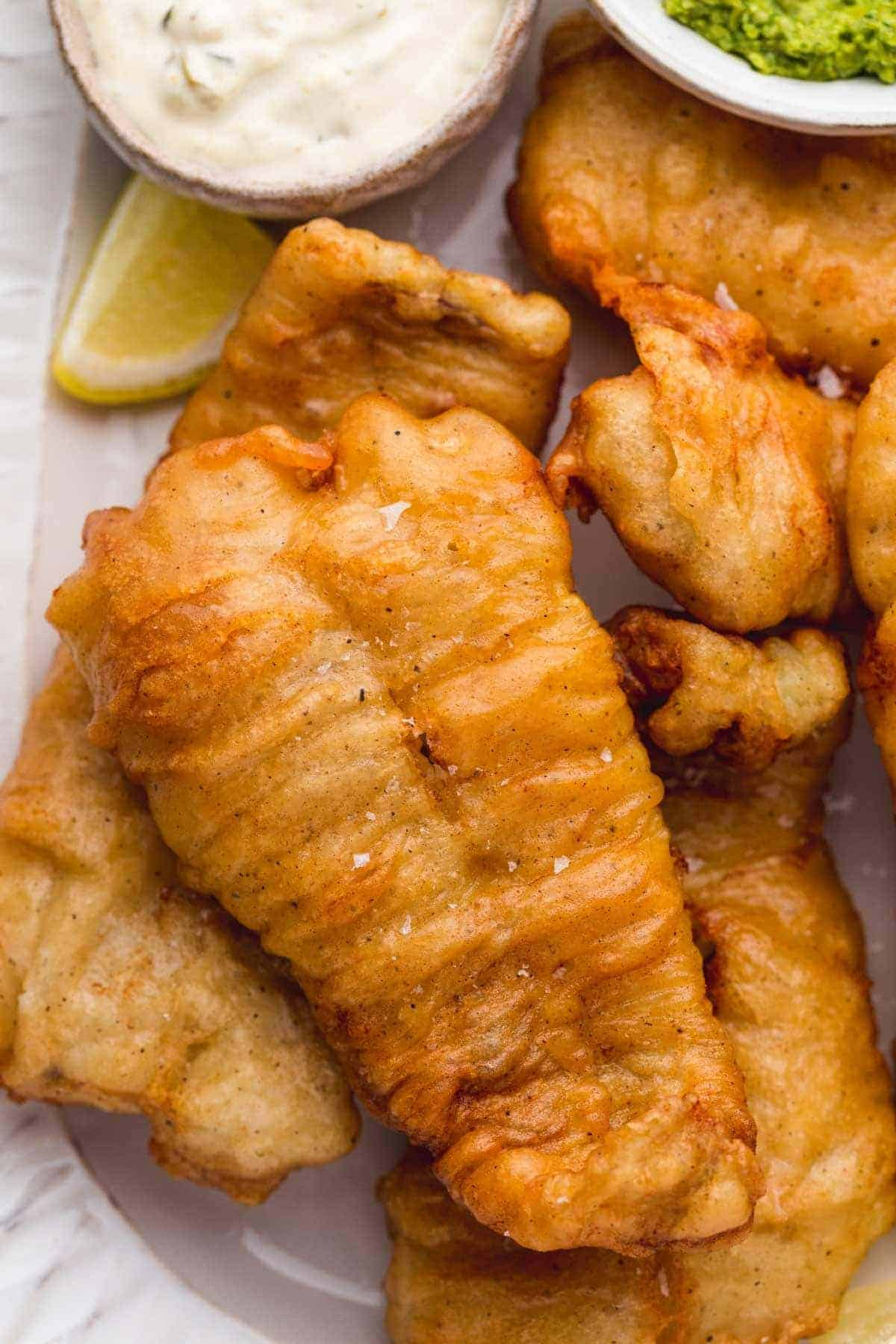 Close up of perfectly crisp golden beer battered fish served on a white plate