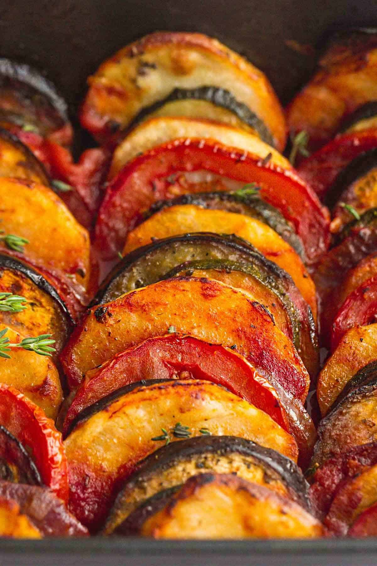 A close up shot of roasted Greek vegetables in a baking dish