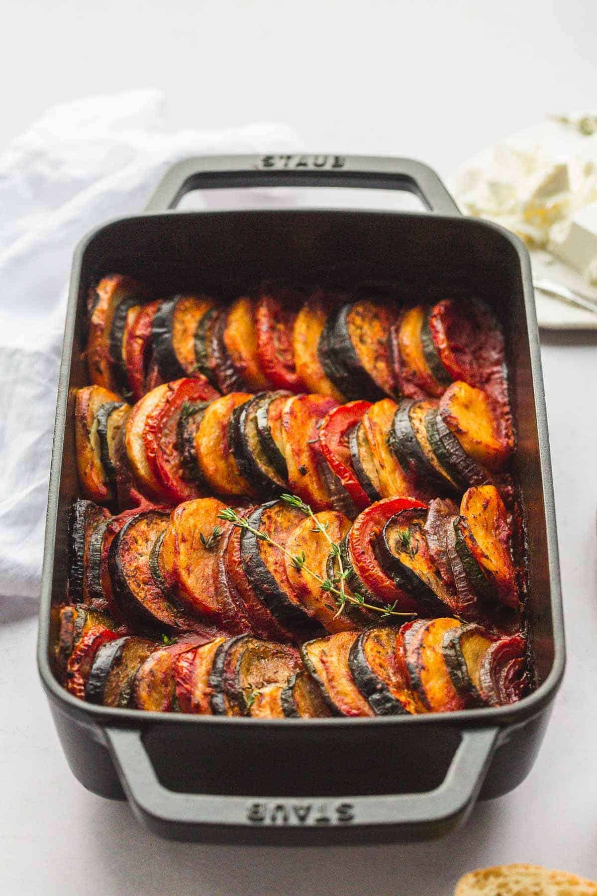 Perfectly roasted Briam vegetables in a black Staub baking dish