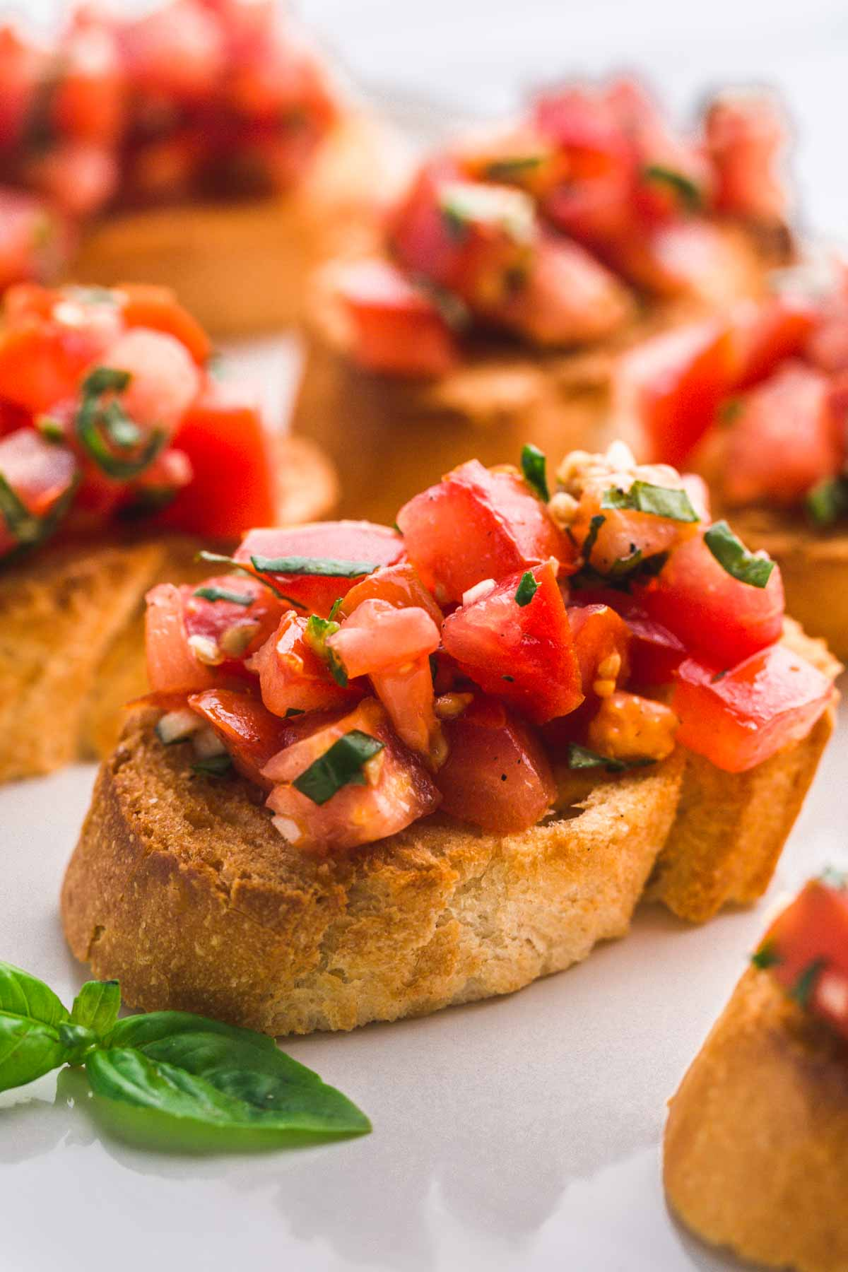 A close up of a Bruschetta topped with tomato basil salad