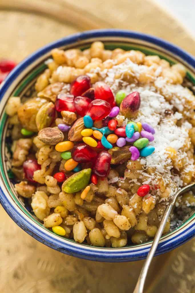 A close up shot of the Burbara in a bowl, with toppings such as pomegranate seeds, pistachios, coconut, and fennel candy.