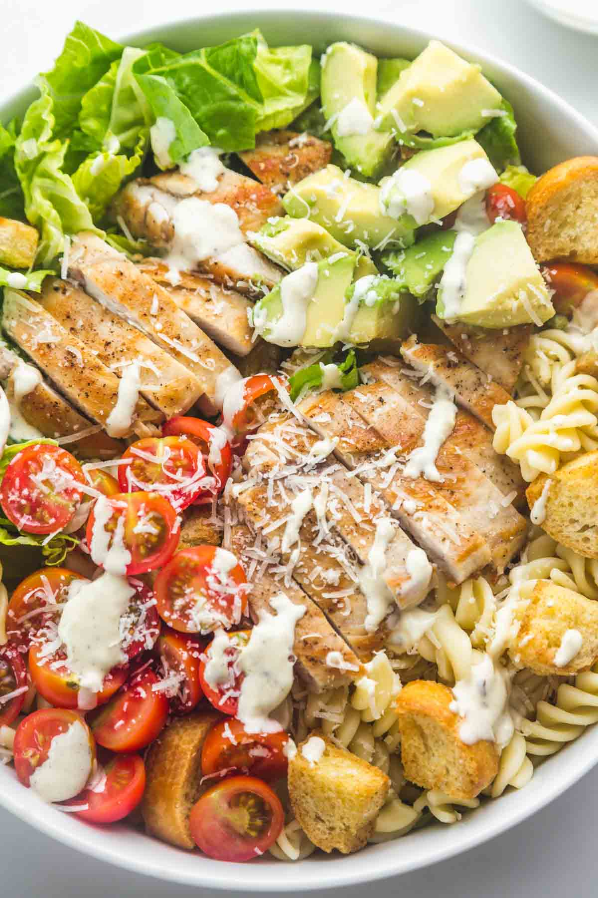 Caesar pasta salad with grilled chicken in a salad bowl, drizzled with caesar dressing