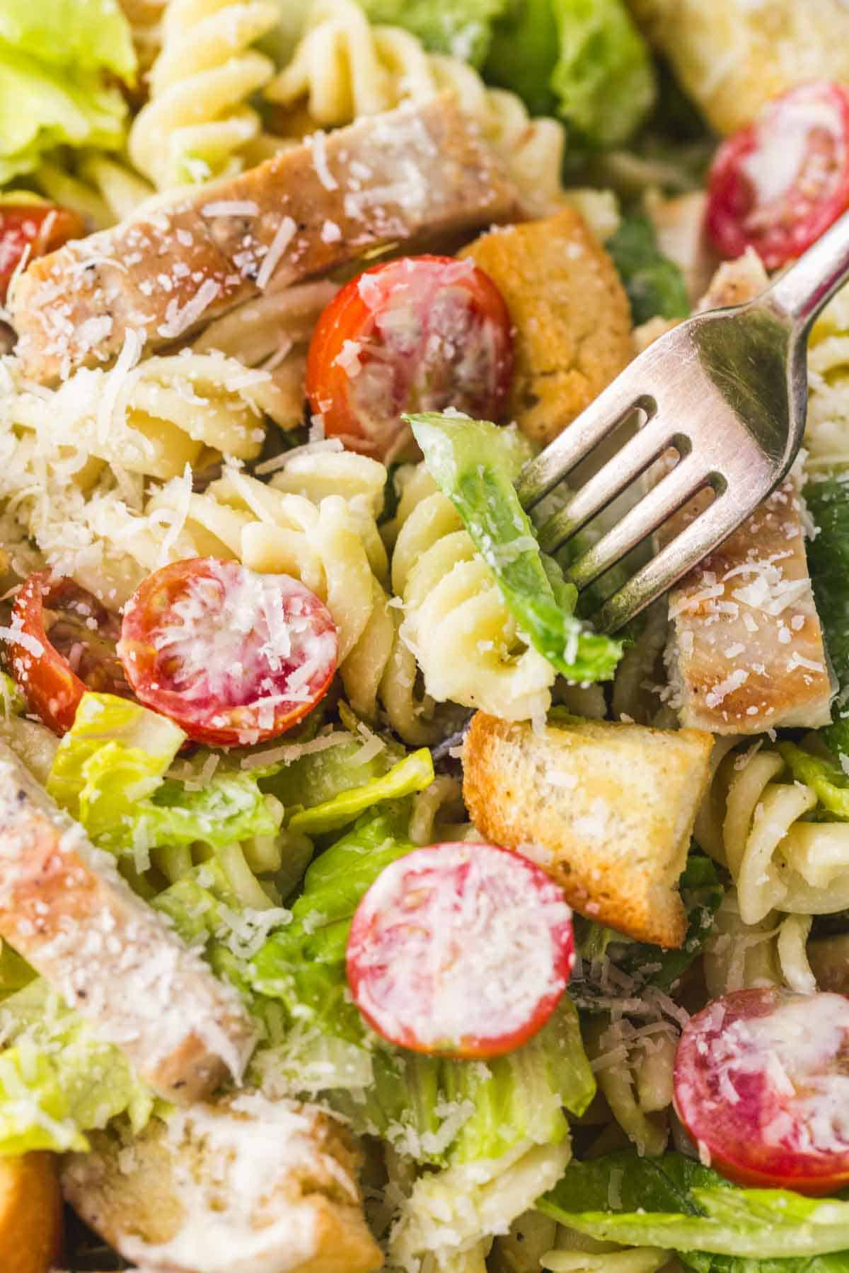 Eating Caesar chicken pasta salad with a fork, close up shot