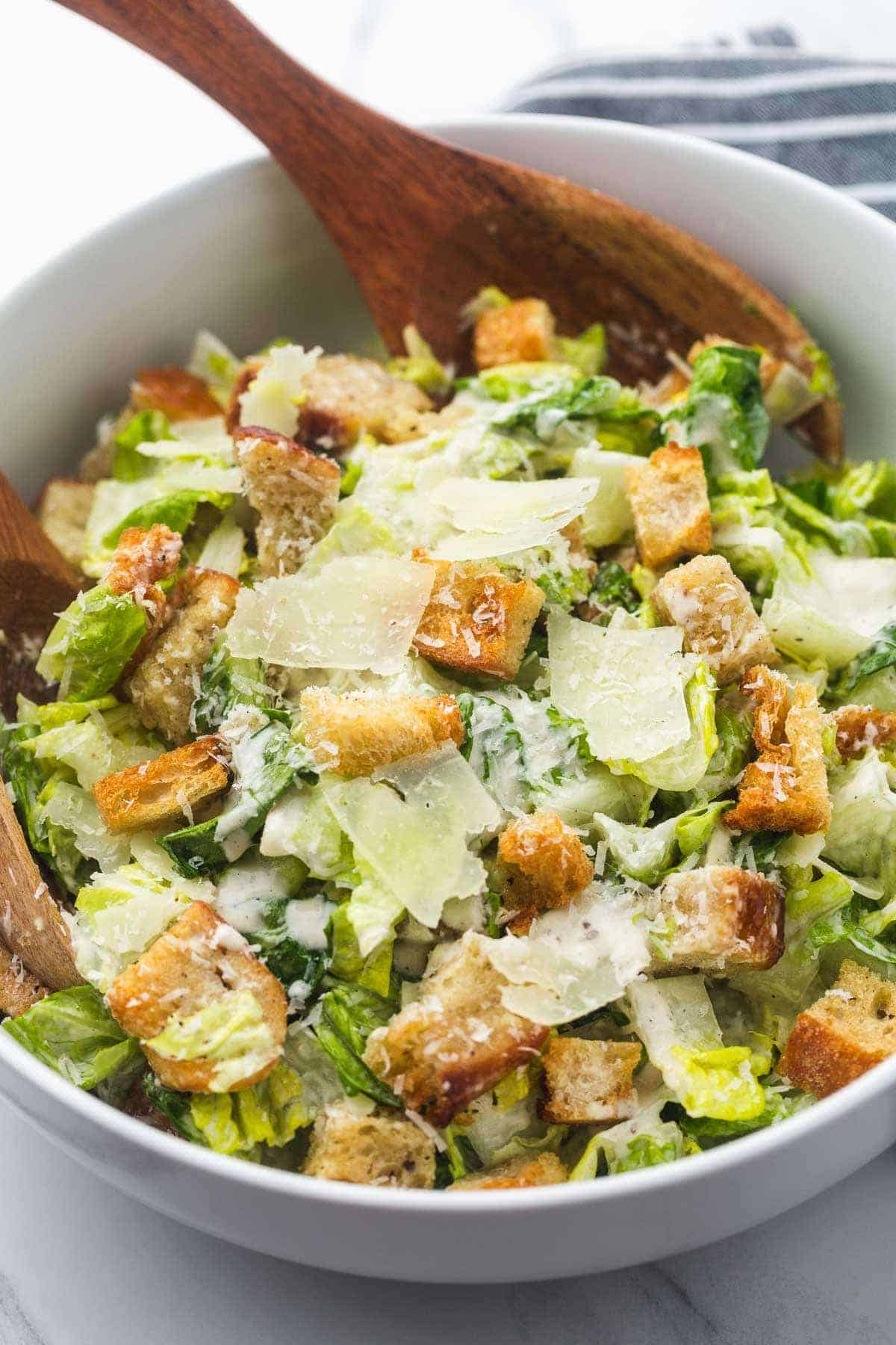 Caesar salad in a large white salad bowl, and wooden salad servers