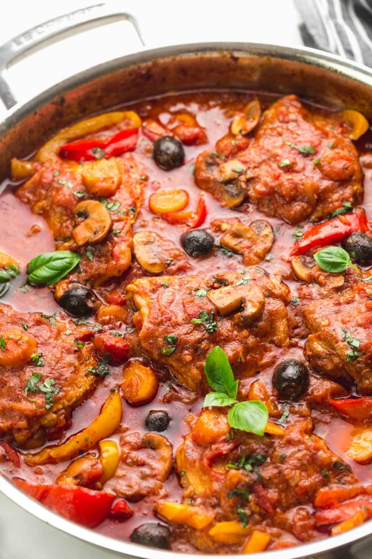 Chicken cacciatore in a skillet, garnished with fresh basil leaves