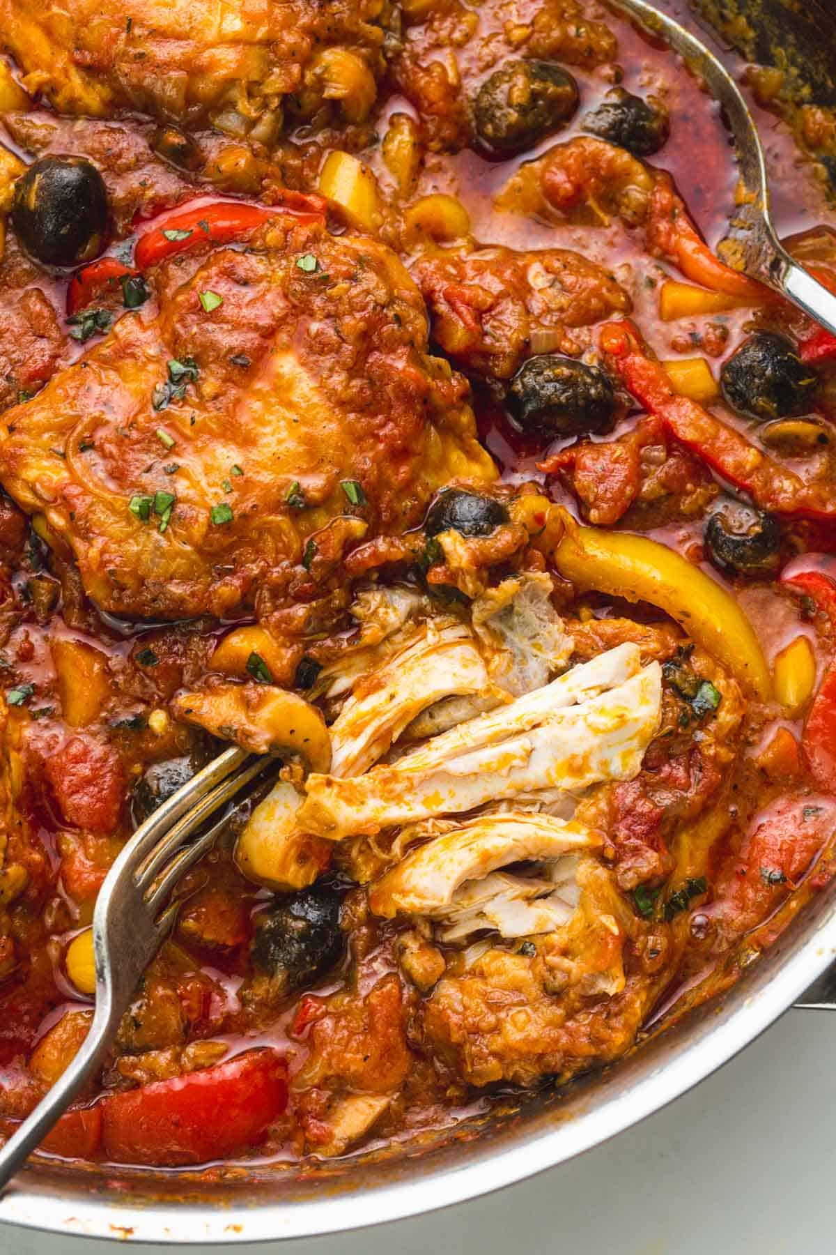 A close up of chicken cacciatore, and fall off the bone chicken to show the doneness of the chicken