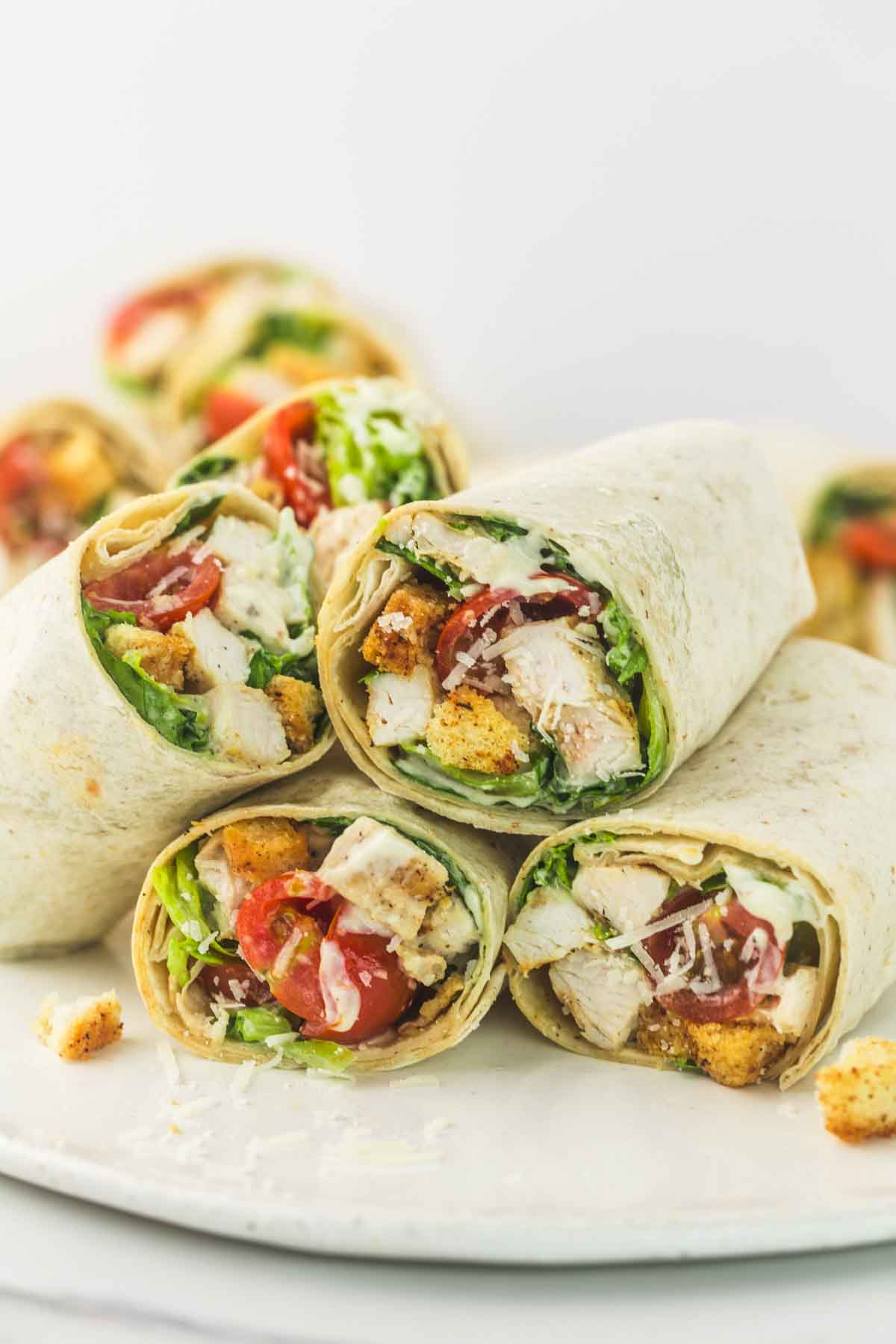 Chicken caesar wraps cut in halves and stacked on each other on a white plate