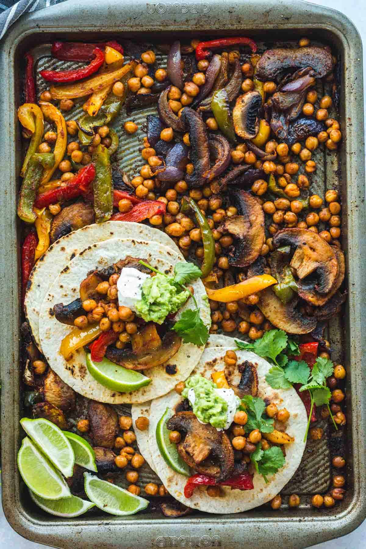 Chickpea Fajitas on a sheet pan with tortilla bread, and lime wedges