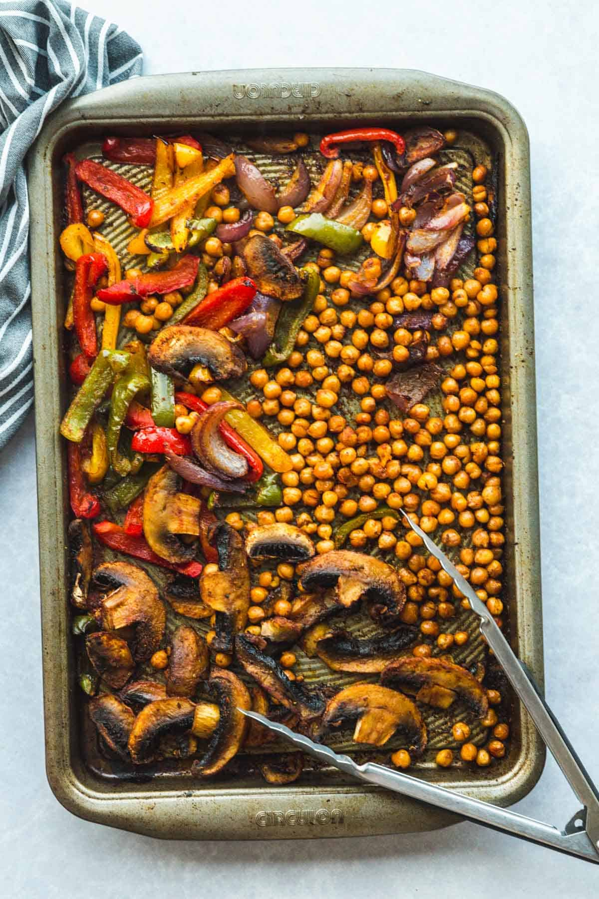 Cooked and ready sheet pan chickpea fajitas with kitchen tongs for serving