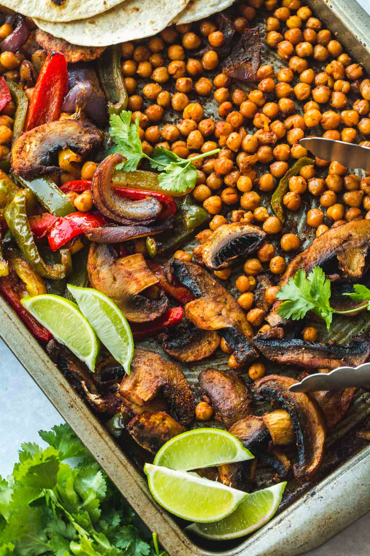 A close up shot of Chickpea Fajitas on a sheet pan with lime wedges