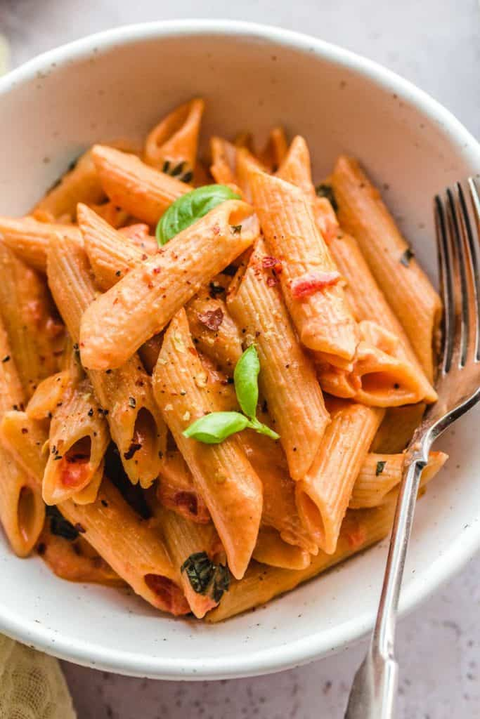 A close up shot of creamy tomato pasta in a bowl with a fork on the side