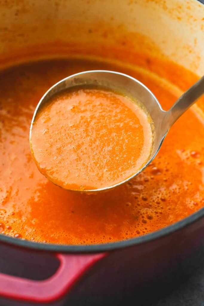 A metallic ladle with tomato soup and a red pot
