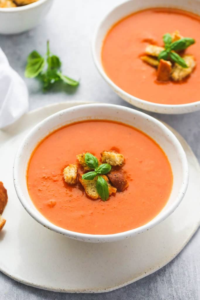 tomato soup in a 2 white bowls, with garlic croutons and fresh basil leaves