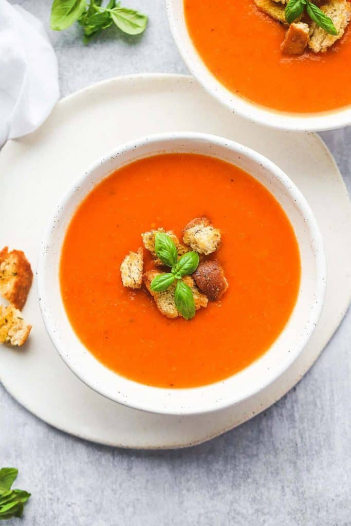 2 white bowls with tomato soup topped with croutons and basil leaves
