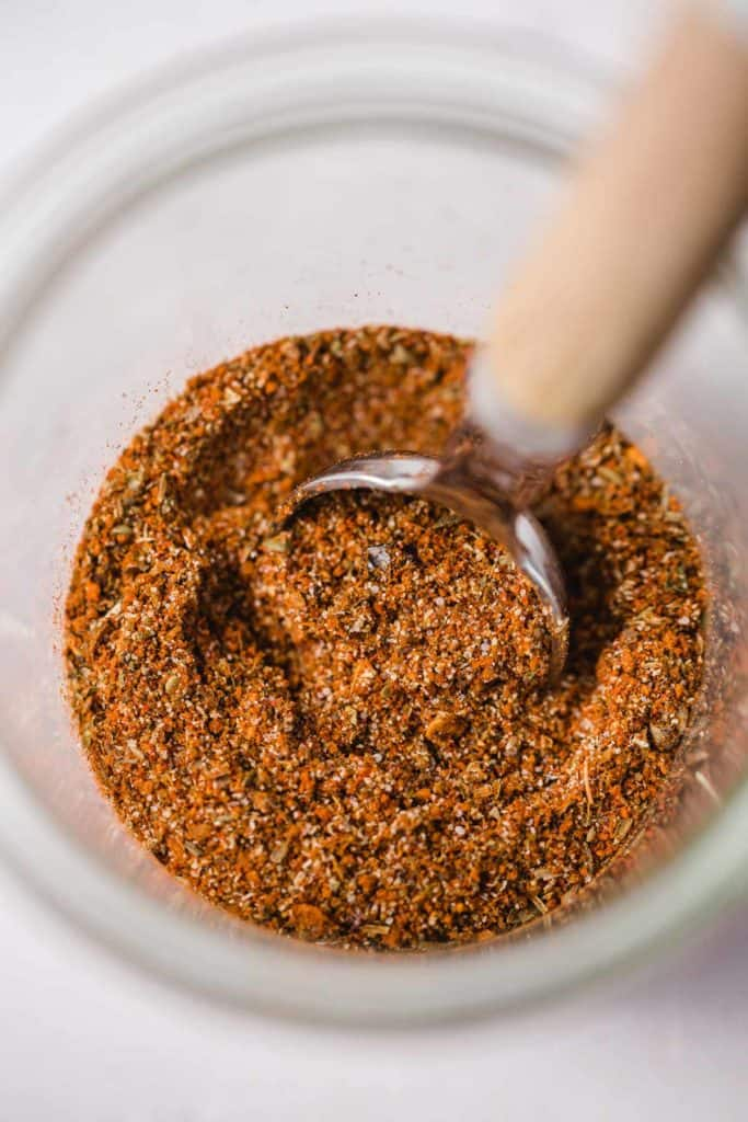A jar of fajita seasoning, and a measuring teaspoon