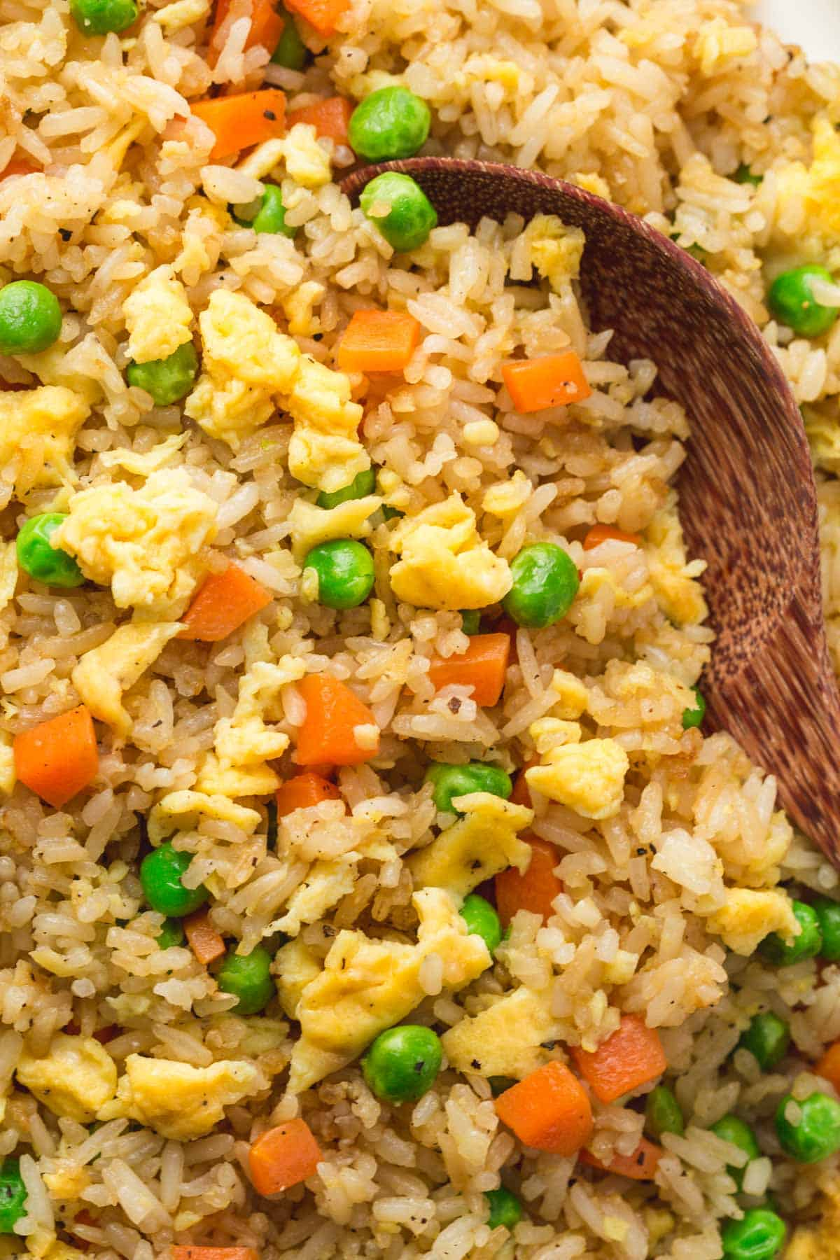 A close up shot of fried rice and a serving spoon