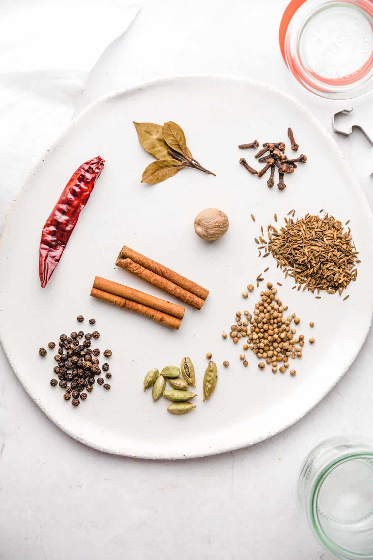 A ceramic white tray with whole spices laid out