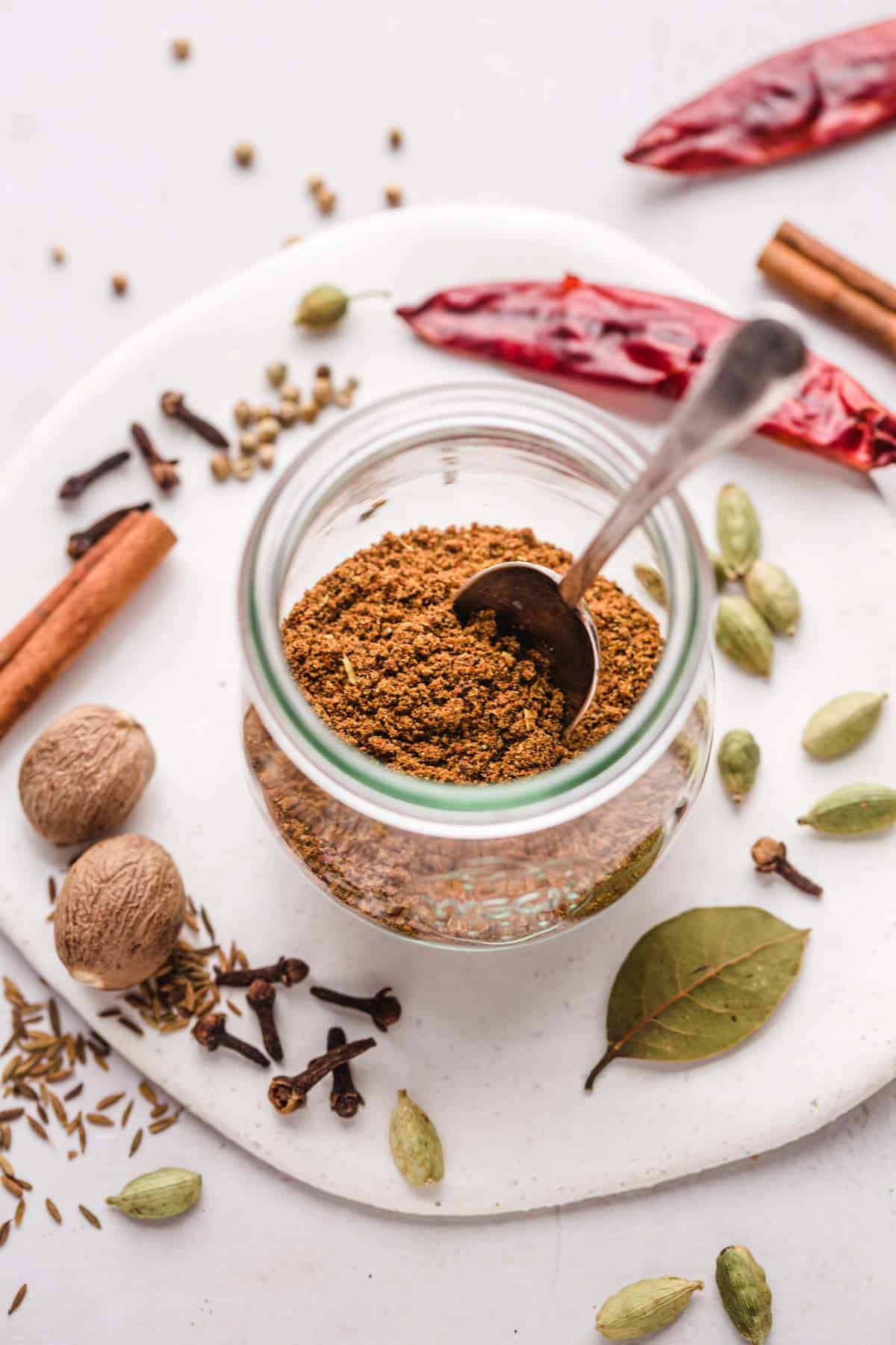A small Weck jar filled with Garam Masala and a small teaspoon