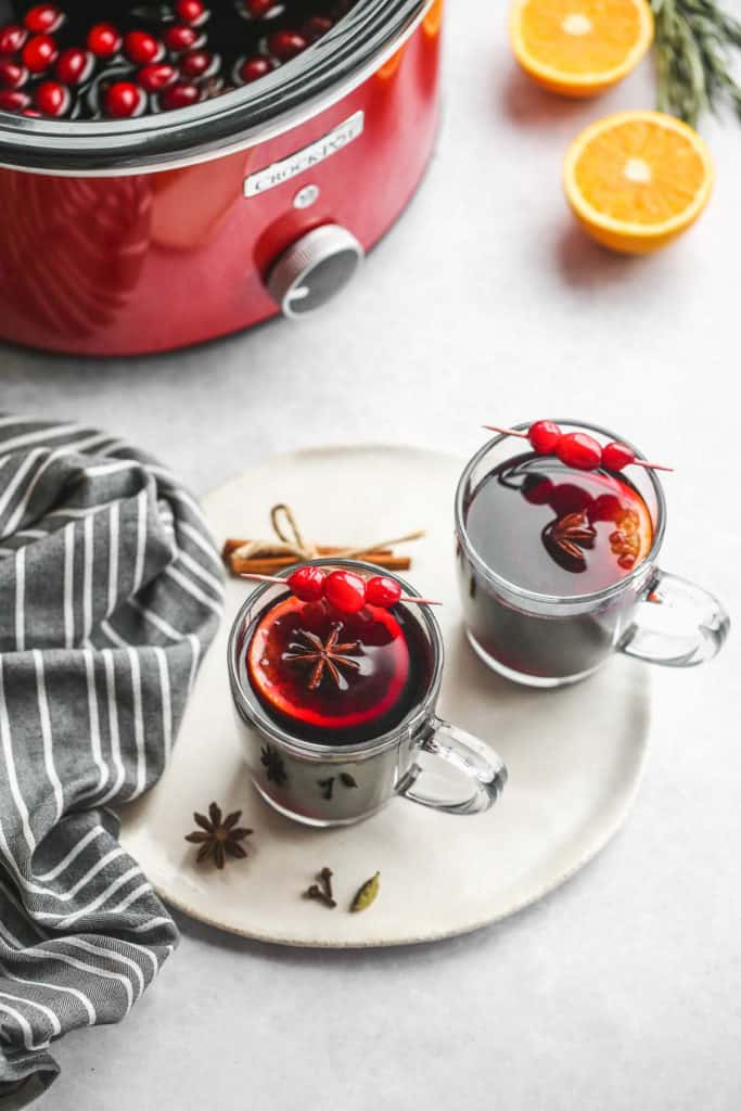 2 mugs of mulled wine with a red crockpot at the back