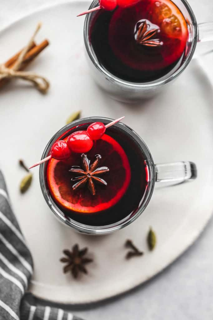 A glass mug filled with mulled wine, a slice of orange, aniseed star, and topped with cranberries on a skewer