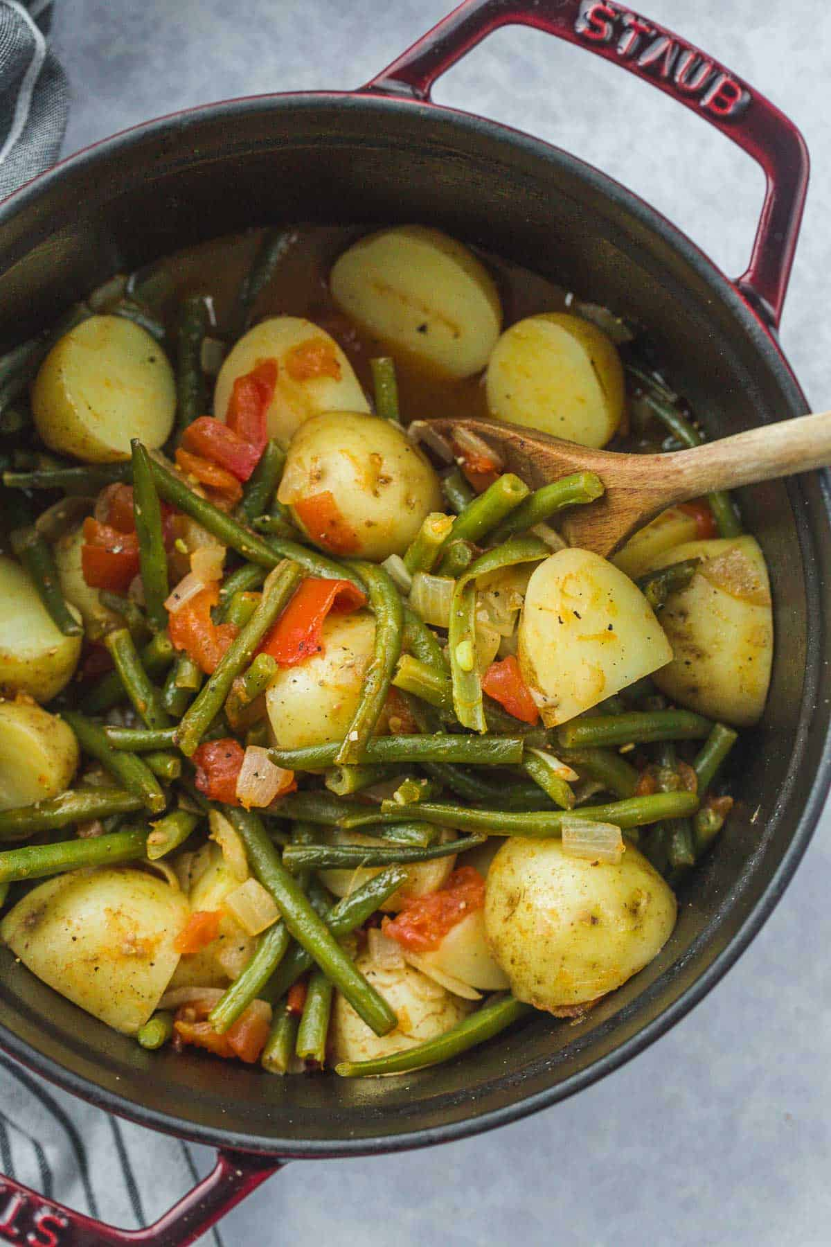 Cooked meal fasolakia in a Staub pot with a wooden spoon