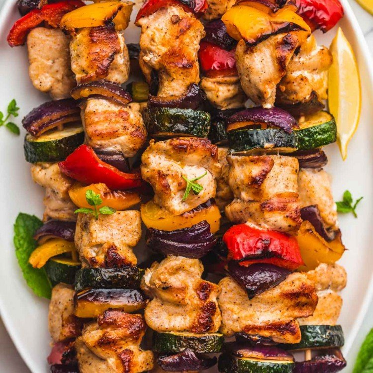 Grilled chicken kabobs with vegetables on a white platter