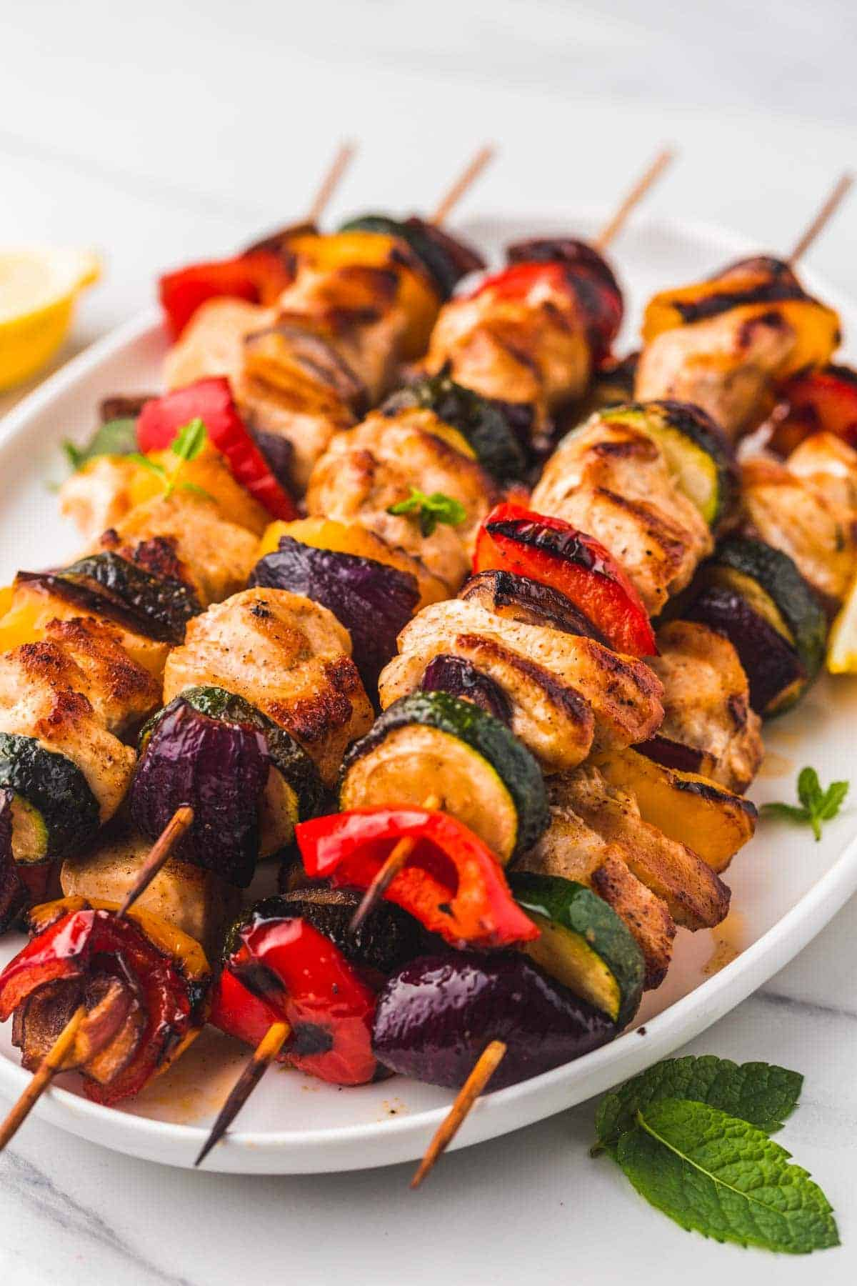 Grilled Chicken Kabobs stacked on an oval serving plate