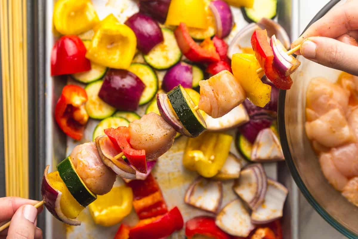 Threading chicken and vegetables on skewers