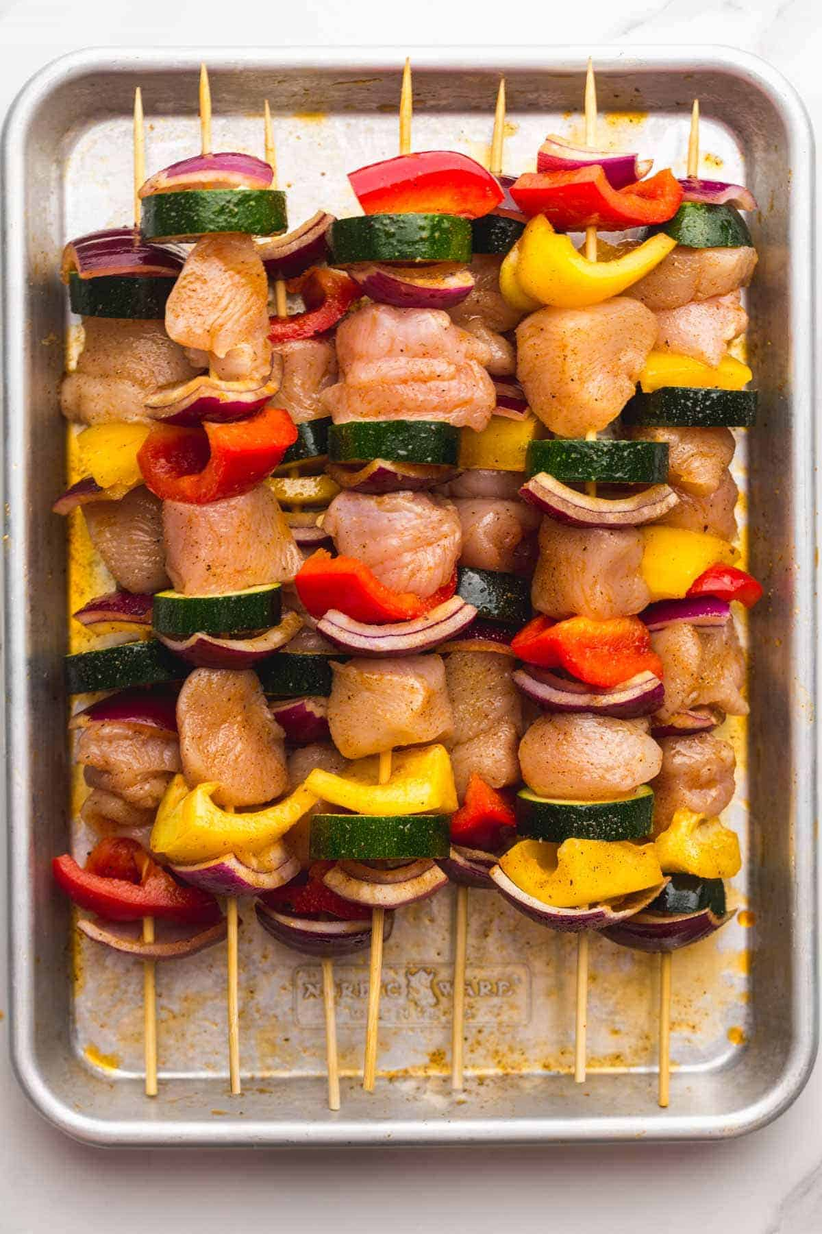 Threaded chicken and vegetable skewers on a sheet pan