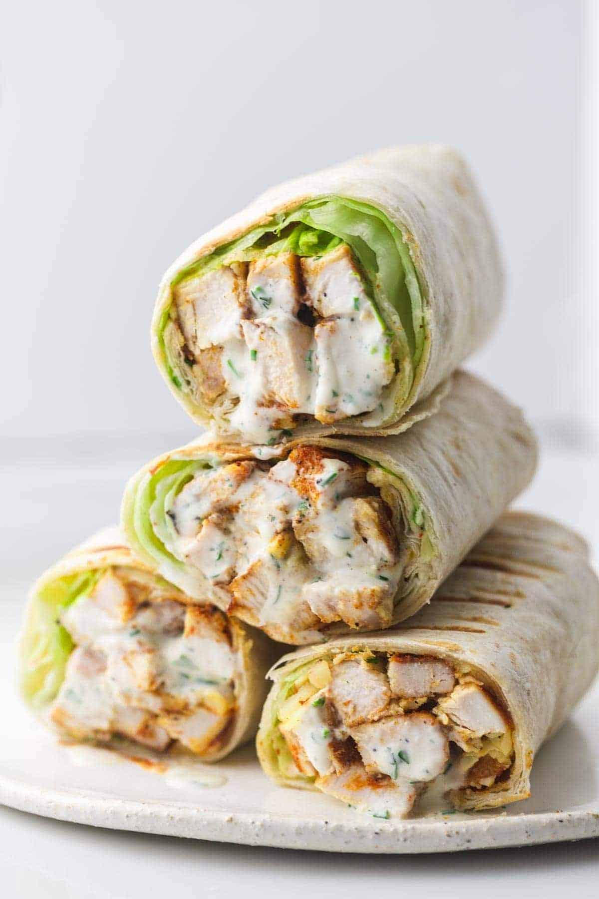 4 grilled chicken wraps stacked on a plate