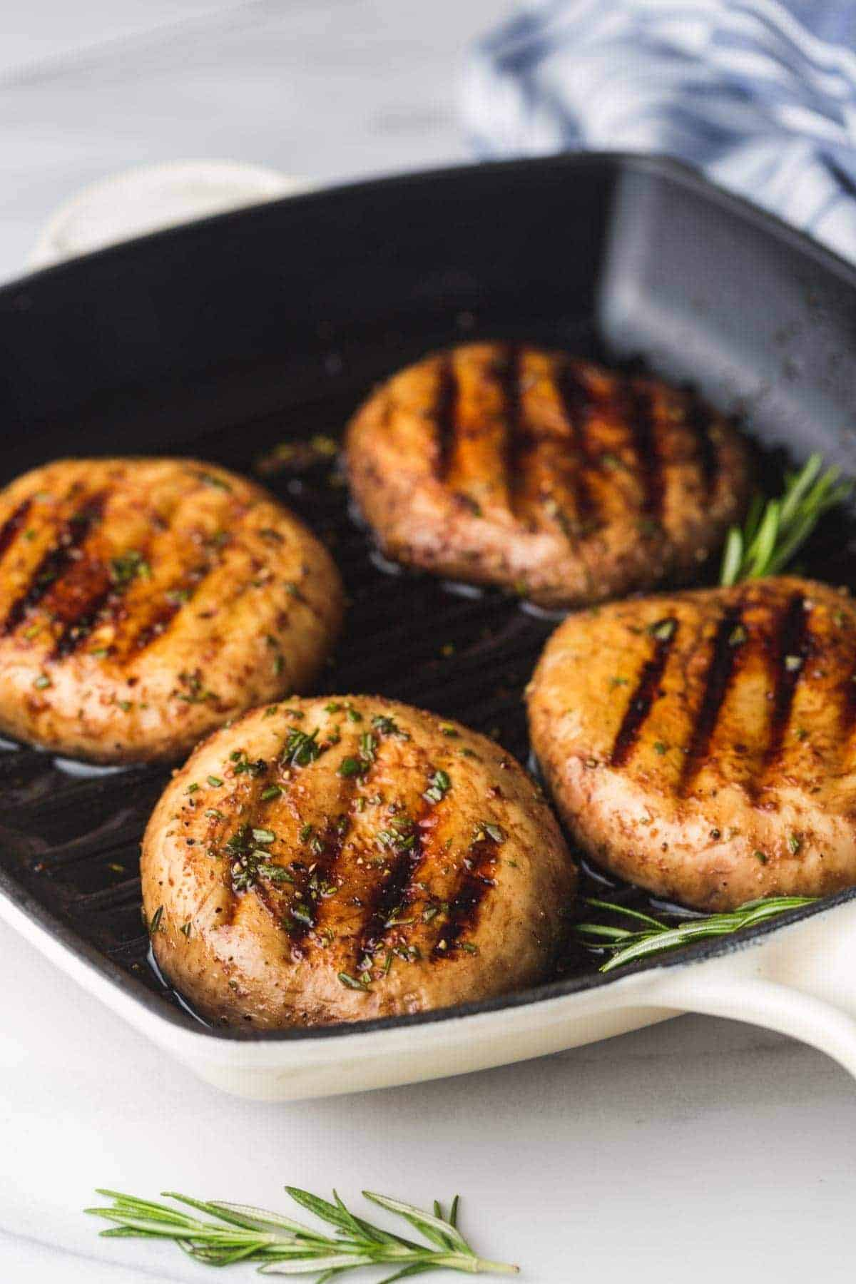 4 Grilled Portobello Mushrooms on a Staub cast iron grill pan with fresh rosemary