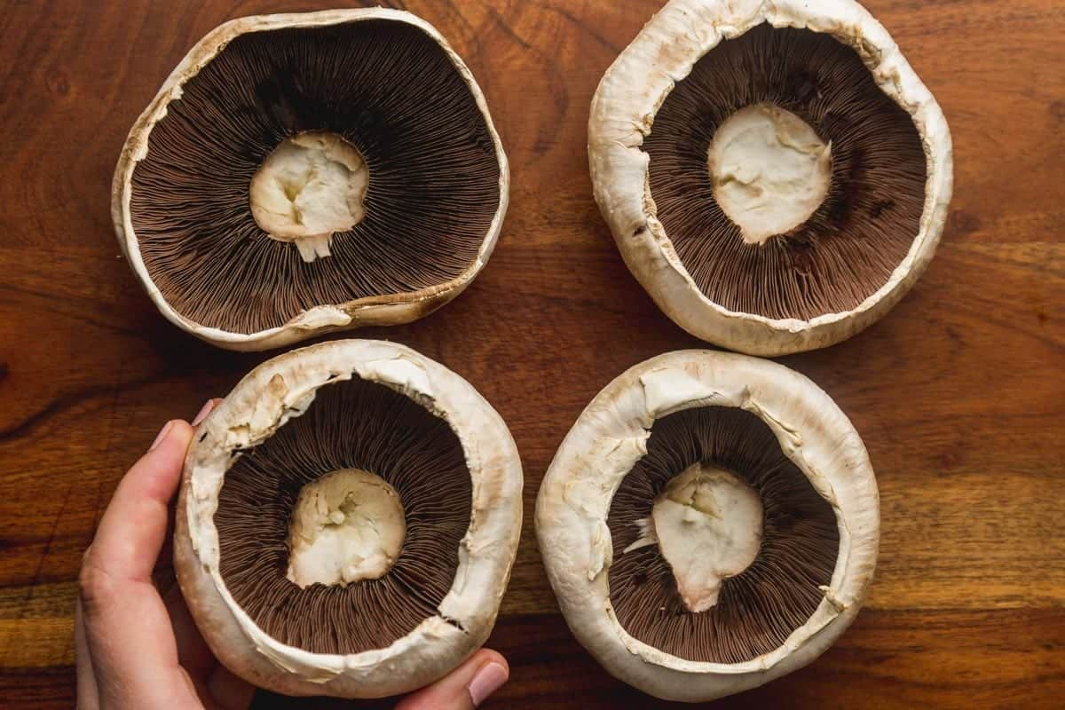 4 white portobello mushrooms on a wooden board with stalks removed