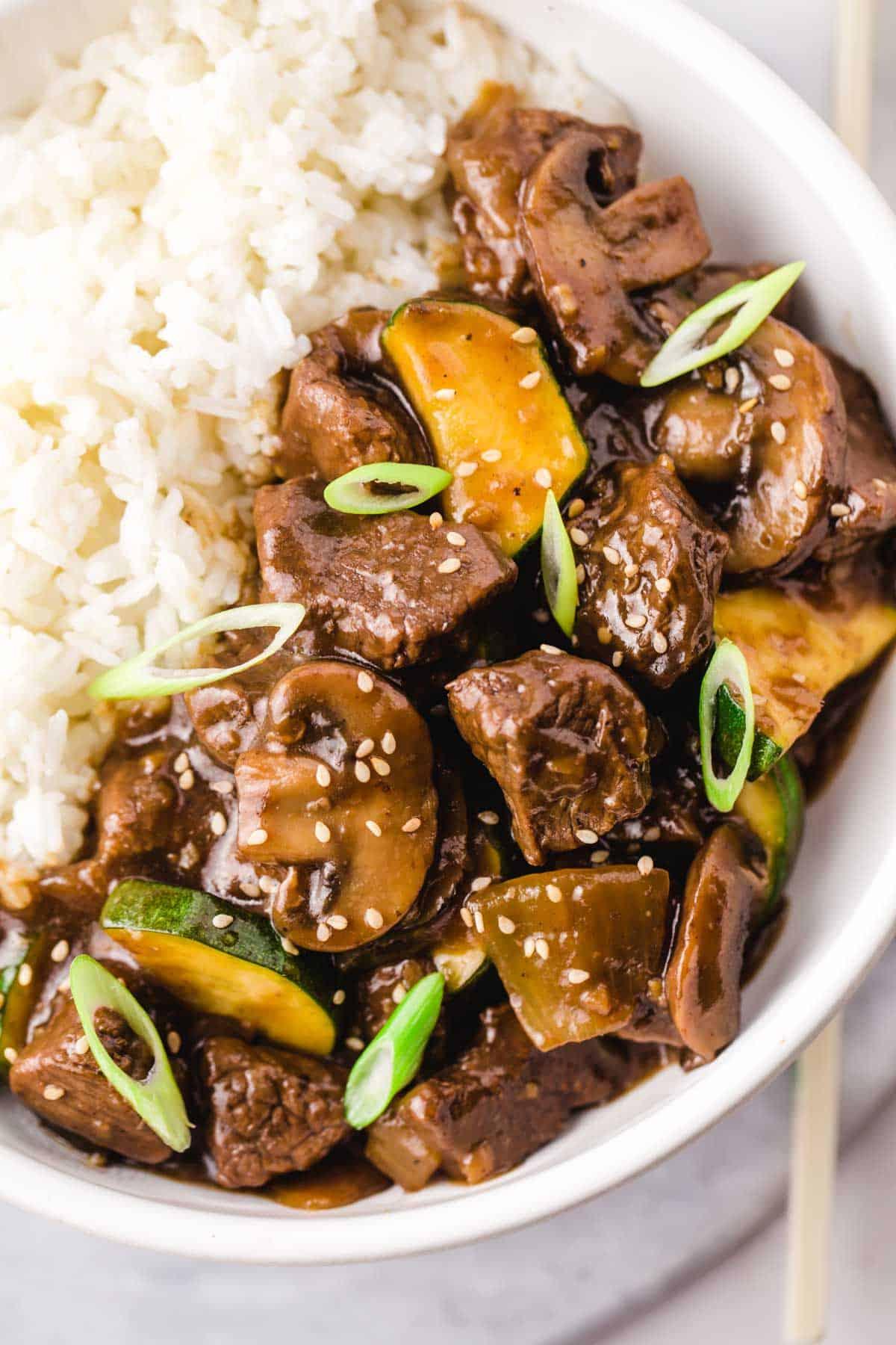 Hibachi steak over jasmine rice in a white bowl