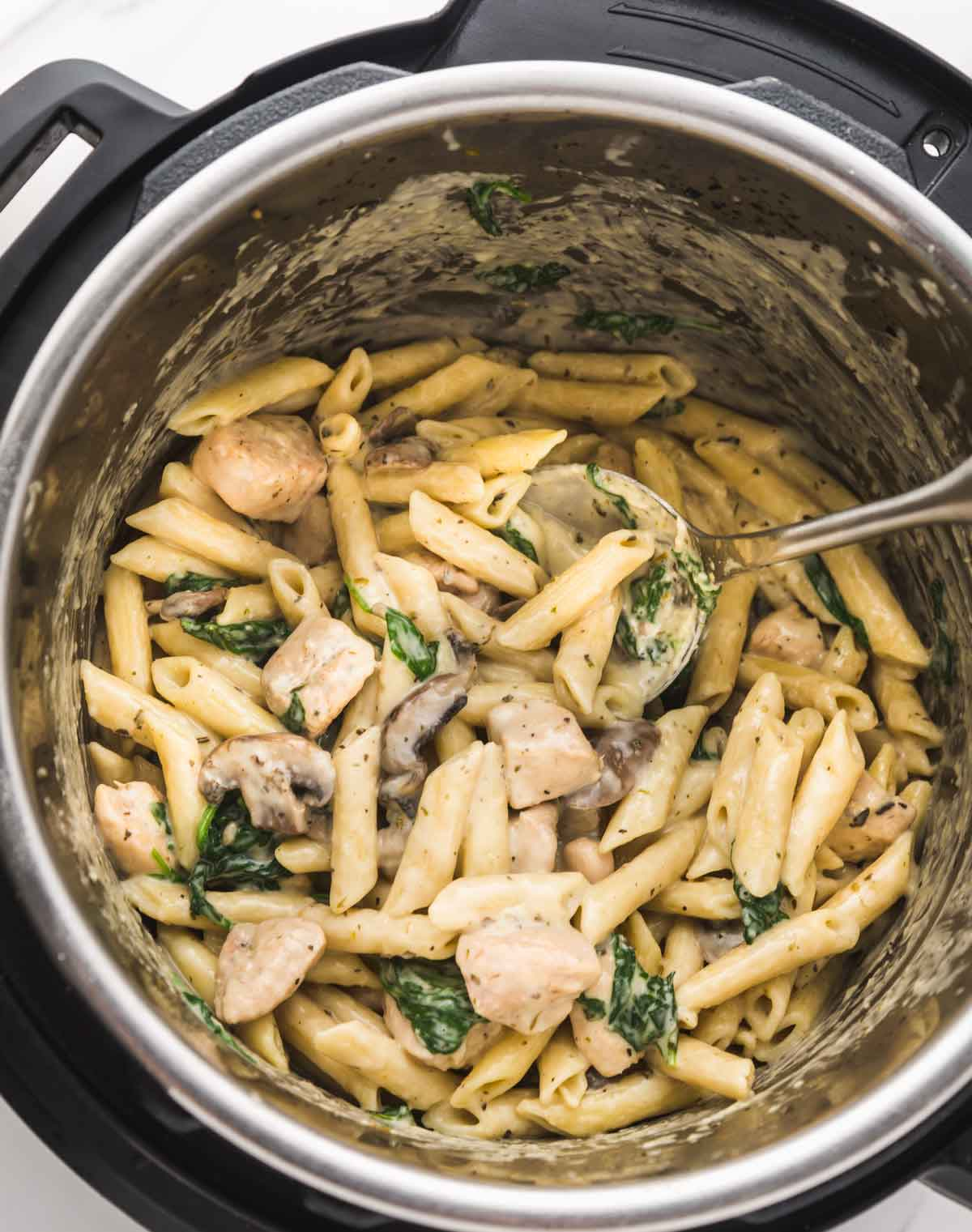 Chicken florentine pasta in the Instant Pot with a serving spoon
